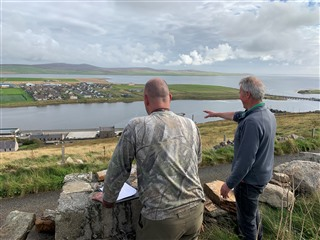 Two trappers looking out over a sloping field and coastline