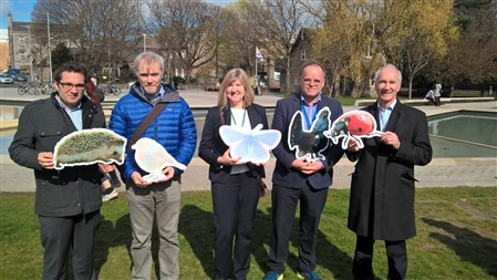MSPs and RSPB Scotland staff pose with photos of wildlife at threat from climate change