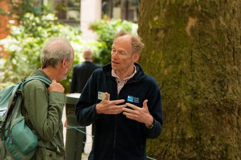 Two men talking passionately about nature in front of a large tree