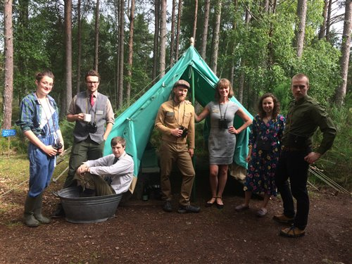 group of people pose in front of tent wearing old fashioned clothing