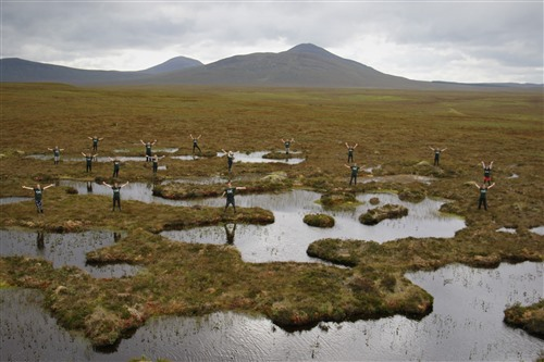 several people standing spread out on the peat bog making celebratory gestures