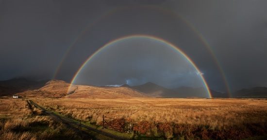 Double rainbow covering mountain range on the Isle of Mull, Scotland.