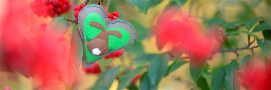 A grey padded heart, with a blue blanket stitch border, depicting the back of a rabbit (complete with white fluffy tail) surrounded by carrots on a green background. The heart is balanced amongst the branches of a bush full of bright red berries.