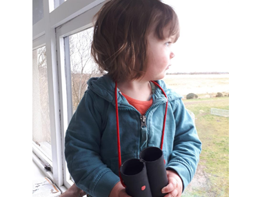 piper with her binoculars looking out window