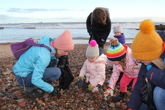 Adults and young children looking at stones on beach