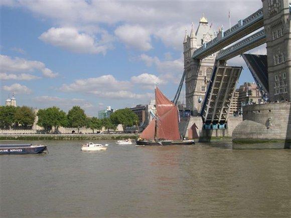A Thames barge glides beneath Tower Bridge